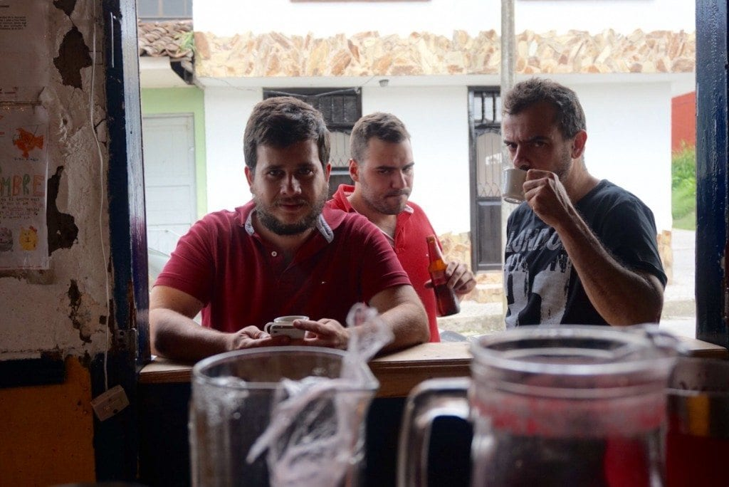 Three men standing in a window, one of them drinking coffee