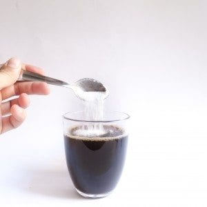 Pouring sugor into coffee