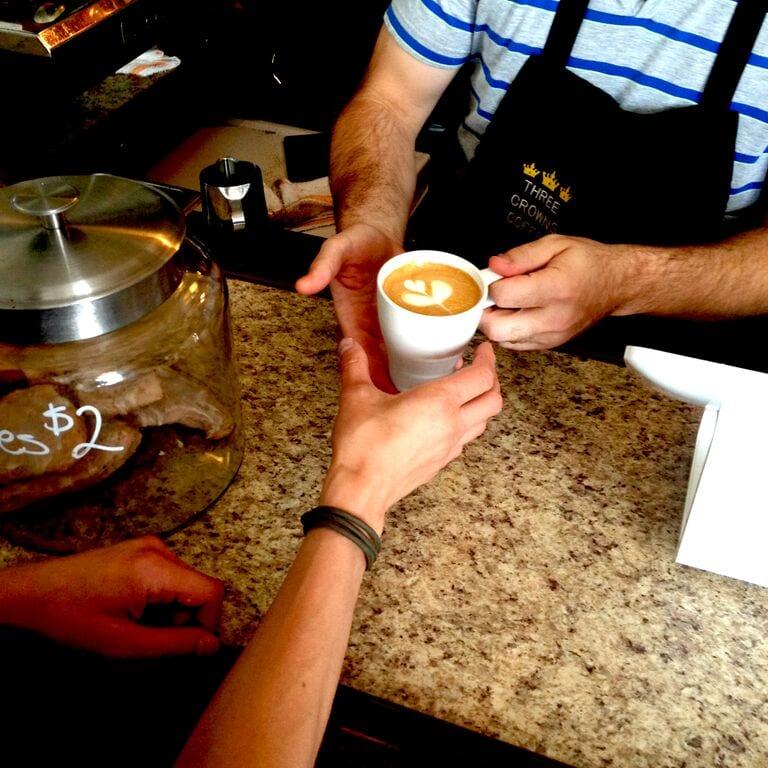 Baroista handing coffee to customer
