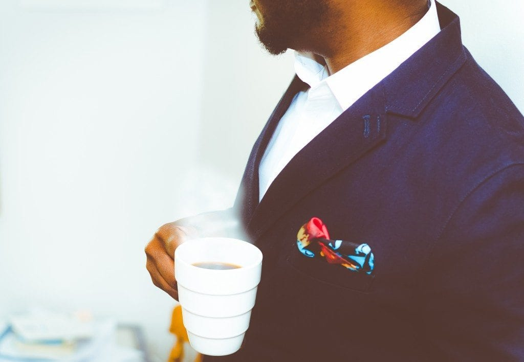 man in suit with a cup of coffee