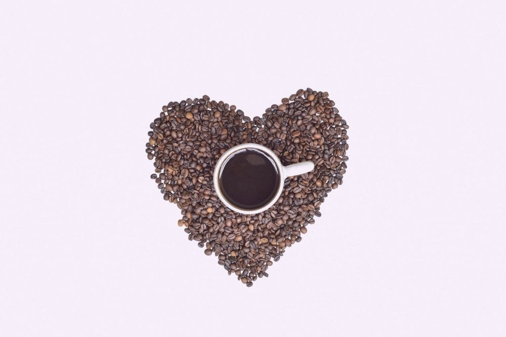 heart made out of coffee beans and cup of coffee
