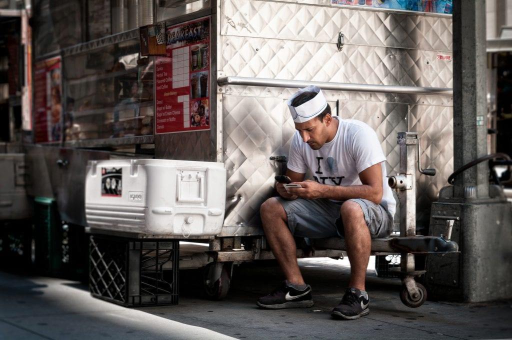 man sitting next to food truck