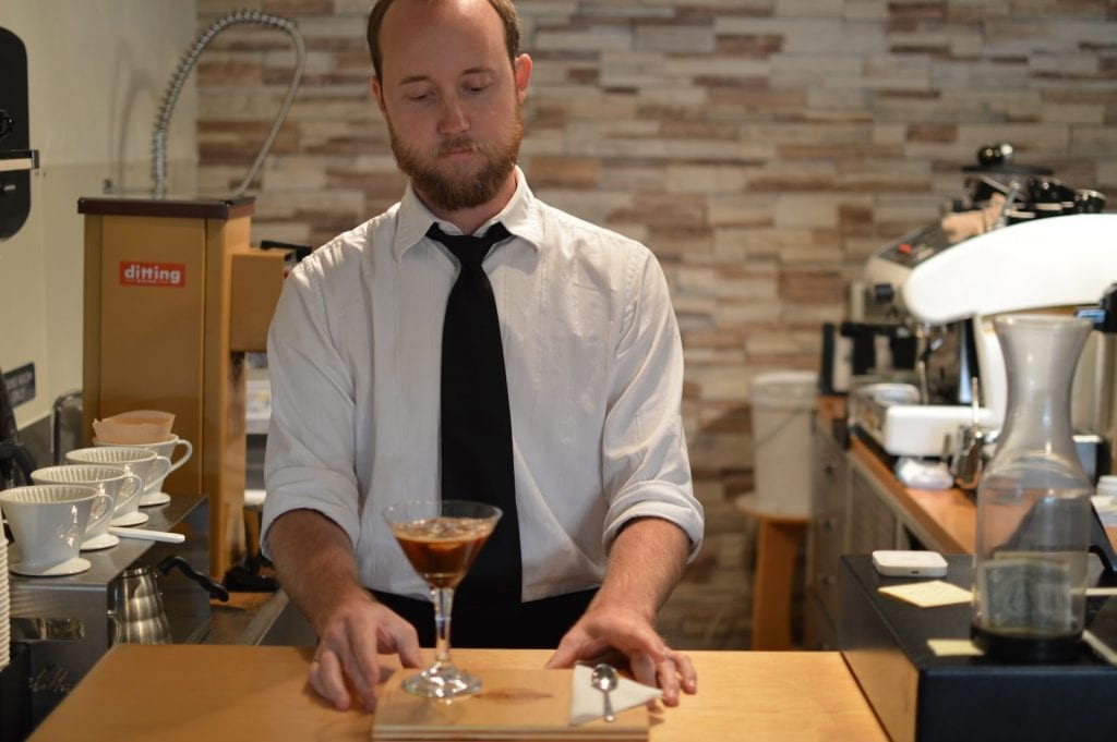 Barista behind bar about to serve coffee-based drink in a martini glass
