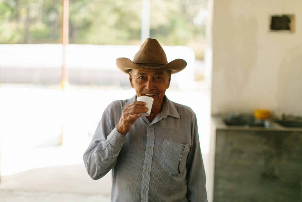 Smiling man drinking from a polystyrene cup with the coffee drying/processing area behind him