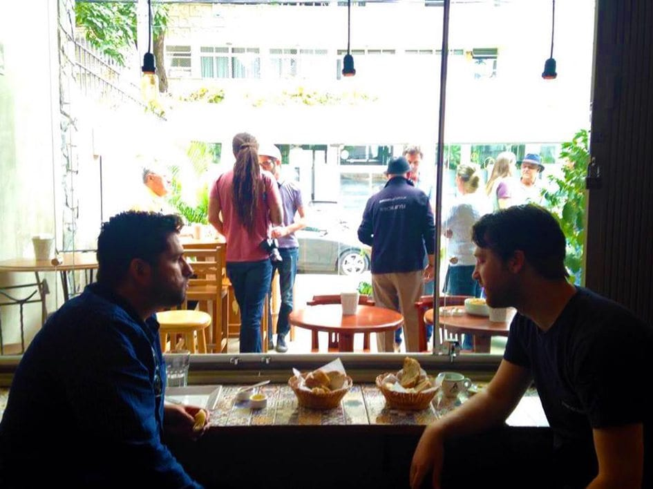 James Tooill and Ricardo of Ally Coffee talking in front of a window
