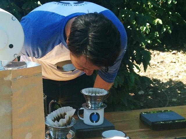 James bends over the coffee he's brewing to smell the aroma