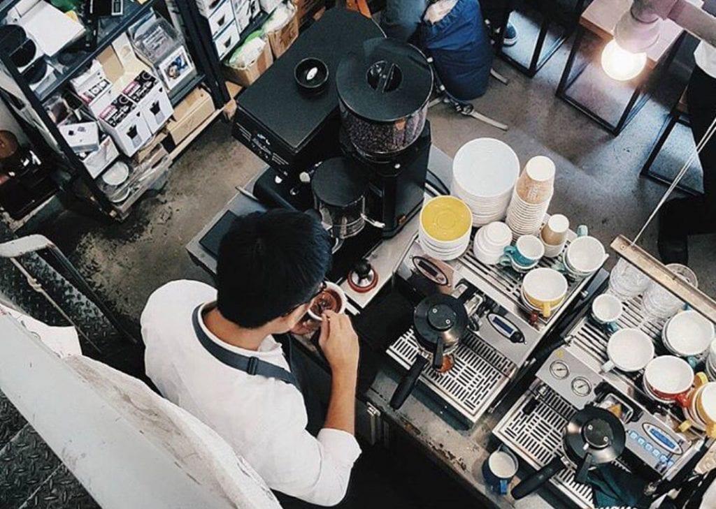 Barista at coffee grinder and espresso machine