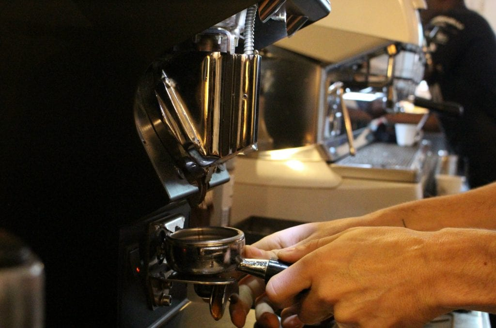 Barista getting coffee from grinder to make espresso