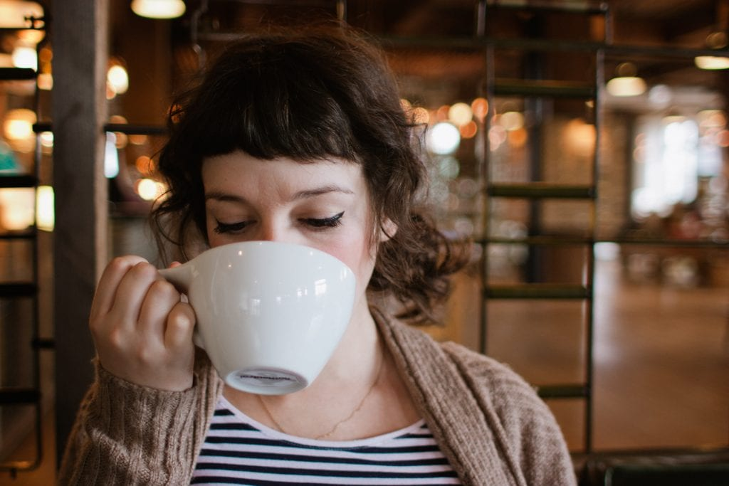 Woman drinks from white coffee mug