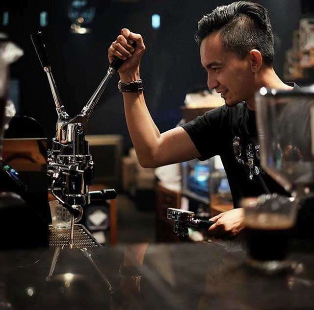 Barista uses lever espresso machine