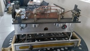 una máquina de espresso antigua con un compresor externo en el fondo