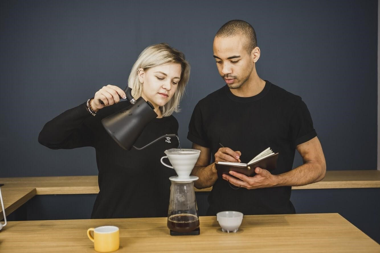 two baristas taking notes while brewing a coffee