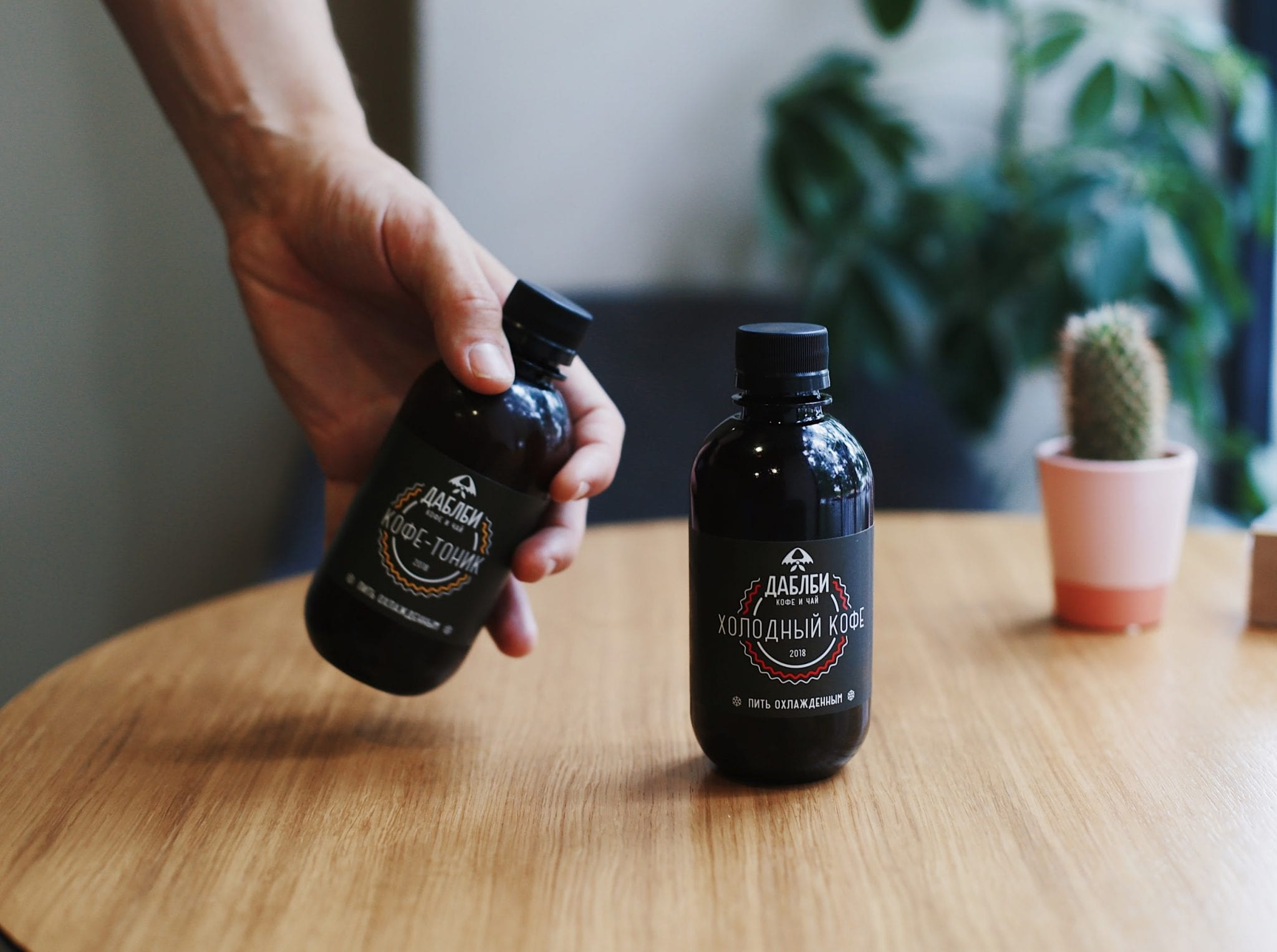 Two bottles of cold brew being shown in a coffee shop