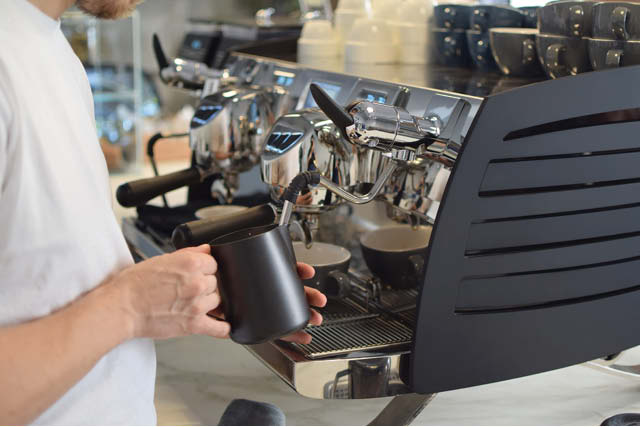 barista steams milk with Simonelli espresso machine