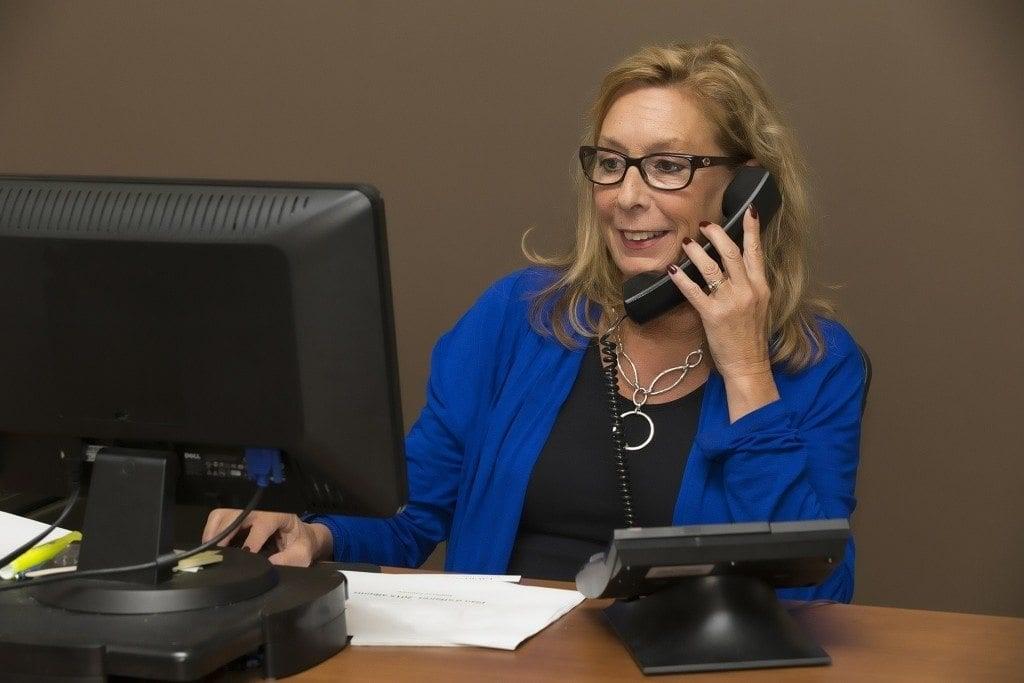 ejecutiva habla con clientes por telefono