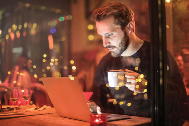 man using laptop drinking coffee