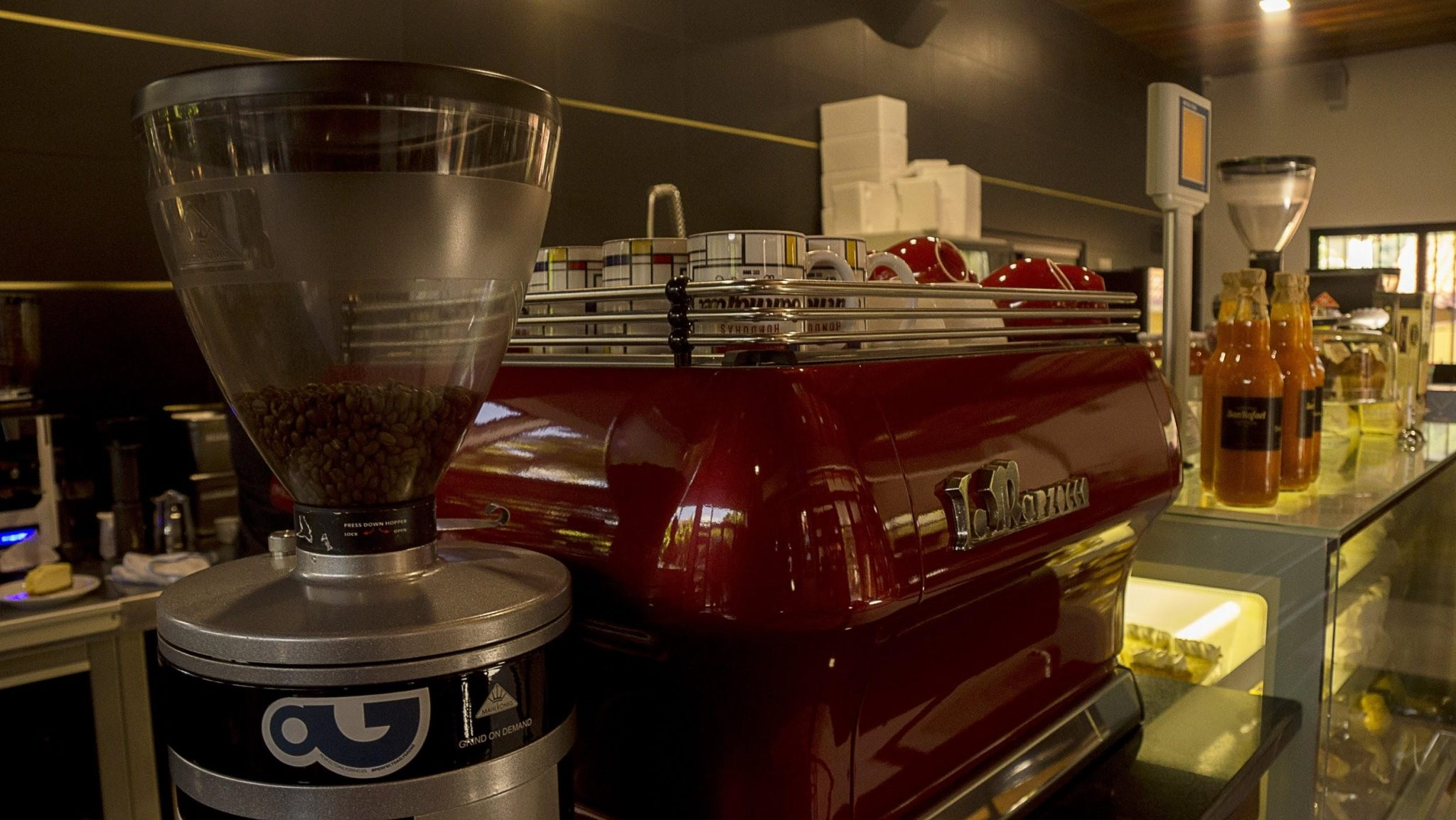 A barista station with a red espresso coffee machine