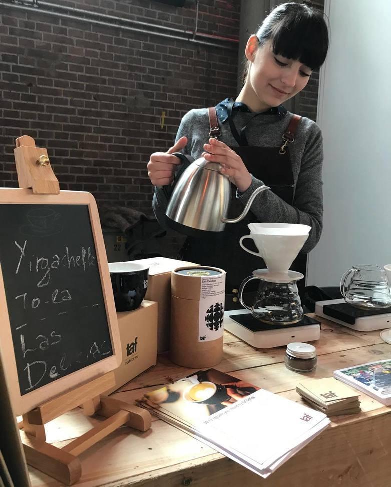 A barista brews fresh coffee on a v60