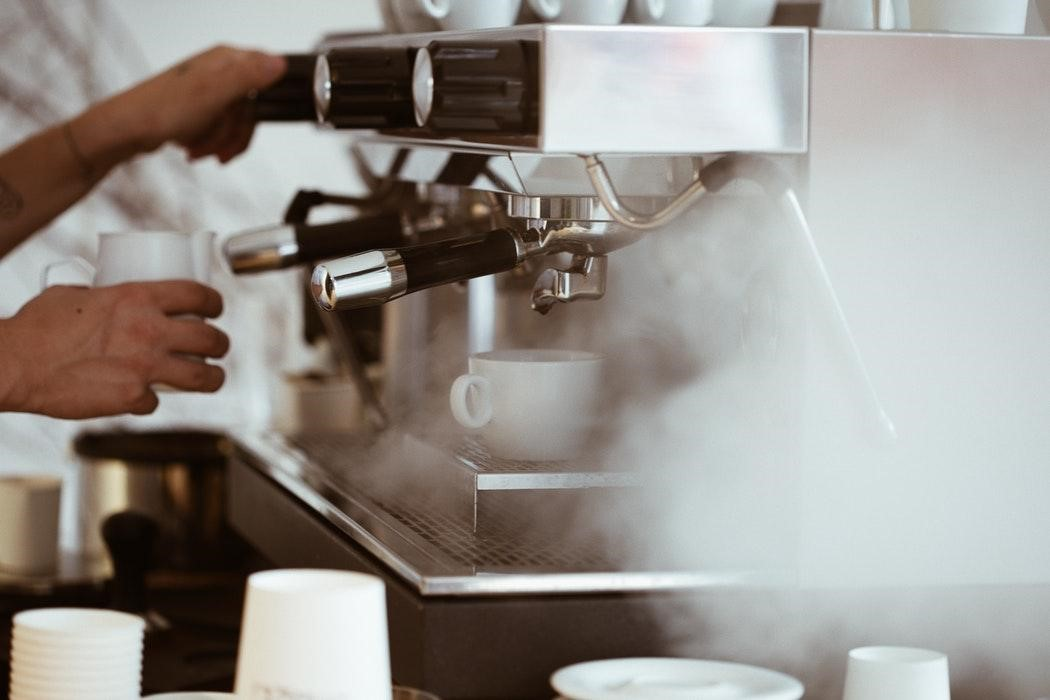 a barista is getting ready the coffee machine to pull some espressos