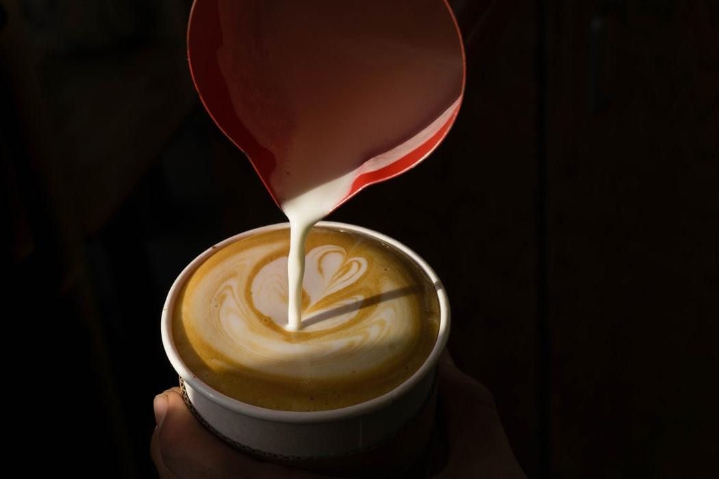 virtiendo leche y haciendo un arte latte
