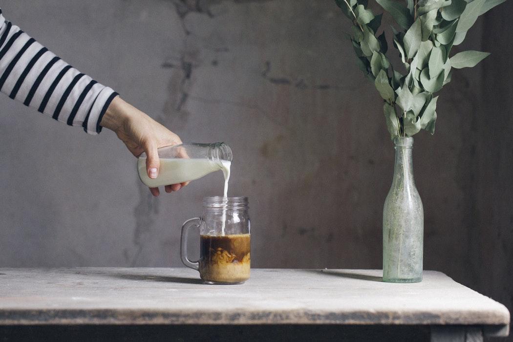 virtiendo leche en un cafe frio para una bebida refrescante