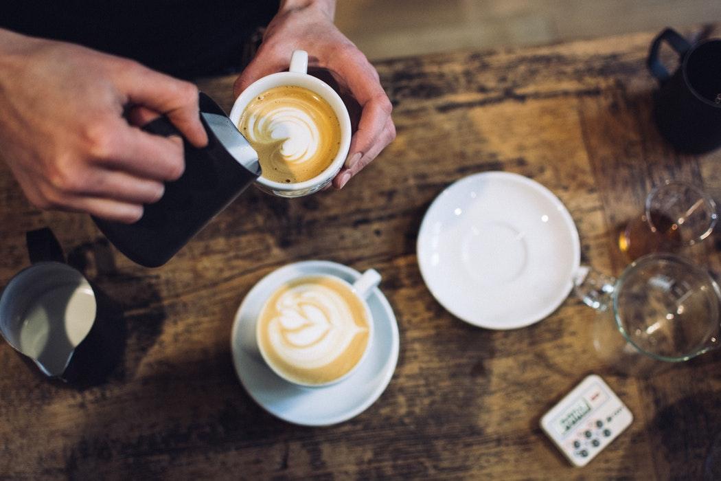 un barista prepara cappuccinos para clientes