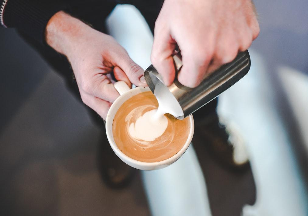 un barista agrega leche recien cremada a un shot de espresso