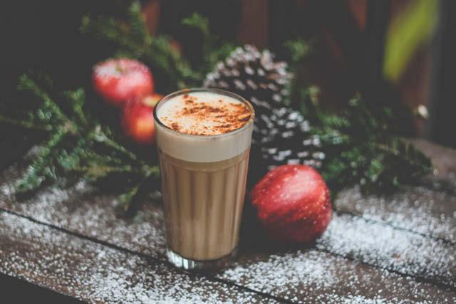 bebida de café caliente junto arreglos navideños