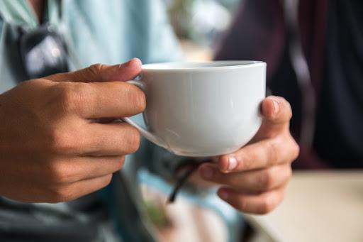 Una taza de cafe en manos de un cliente