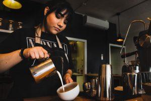 barista pouring milk into cup of espresso
