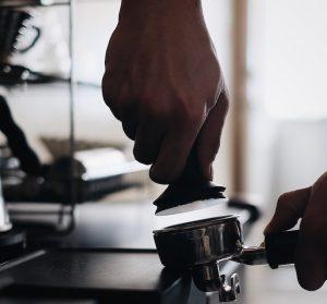 barista tamping coffee in portafilter