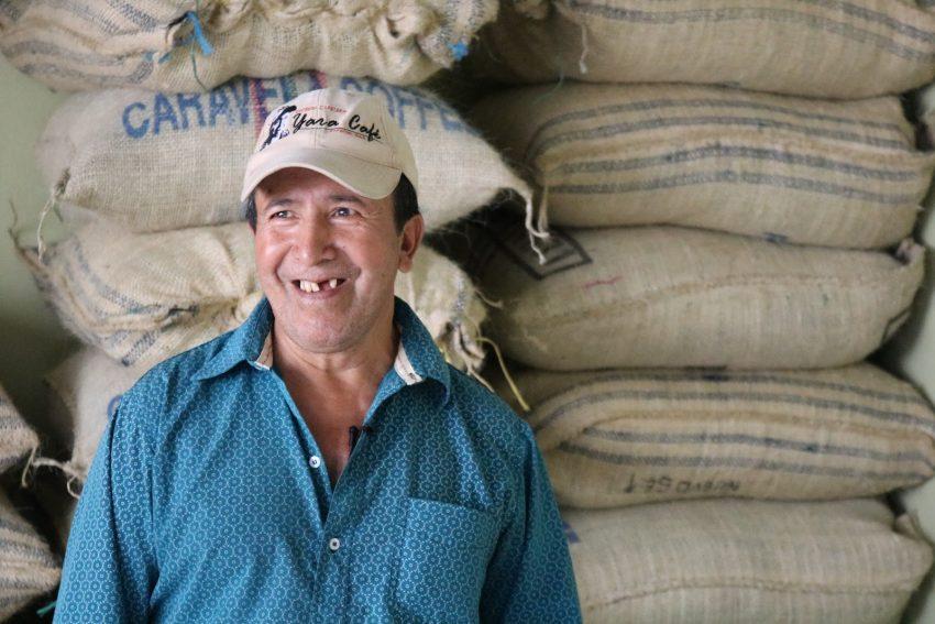 productor de cafe junto con sus sacos de cafe