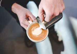 barista pouring latte art into cup of espresso