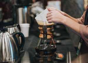Barista removing bleached filter from chemex