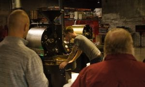 roaster inspecting cooling batch of coffee