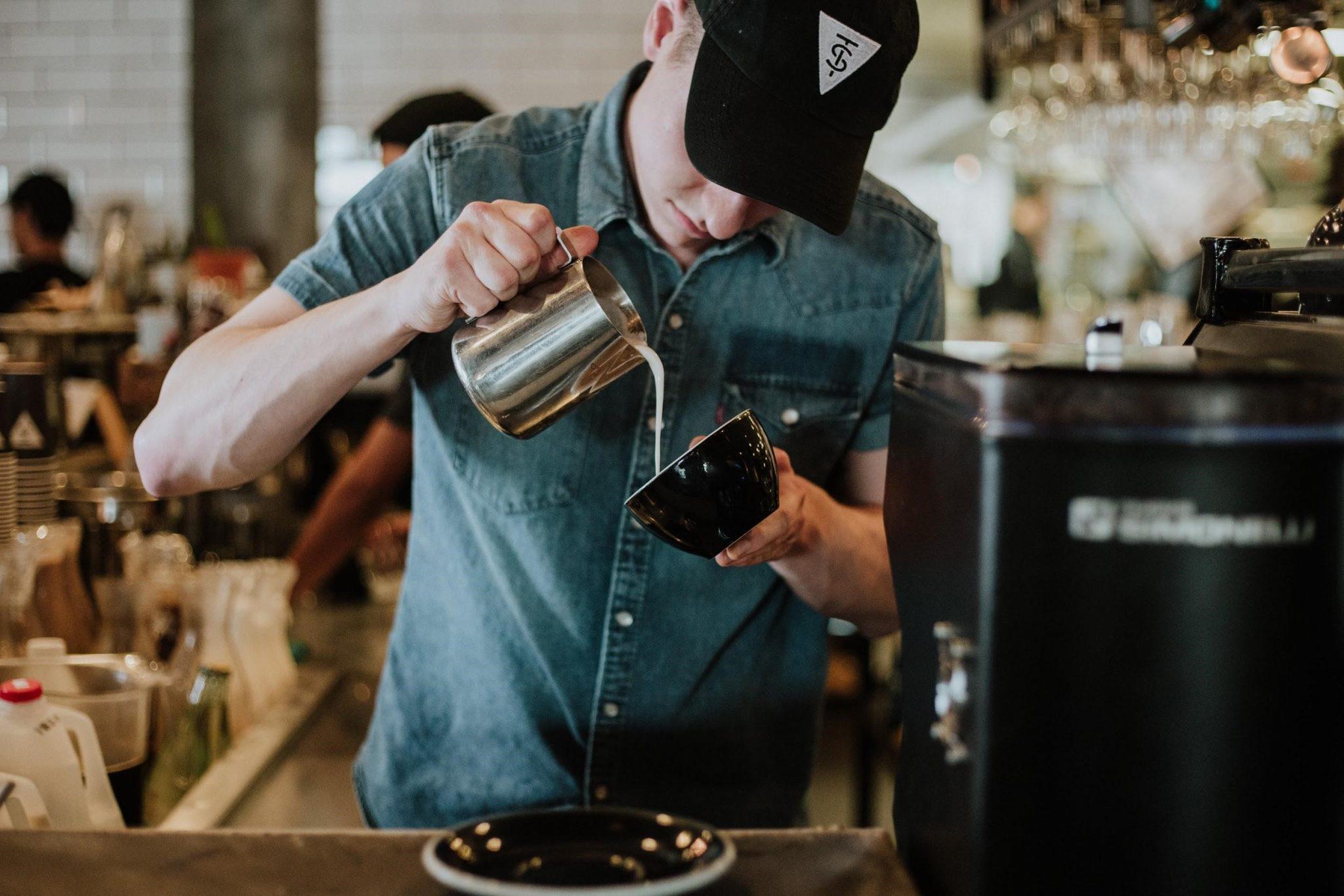 un barista vierte leche en una taza de cafe