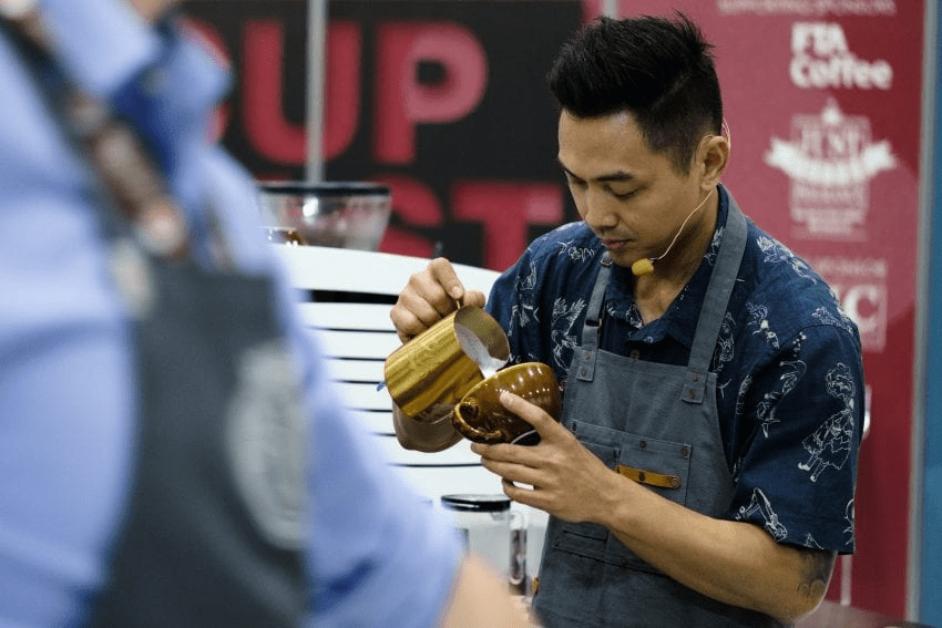 Un barista vierte leche para hacer arte latte