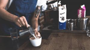 barista poniendo leche a un espresso para hacer un cappuccino