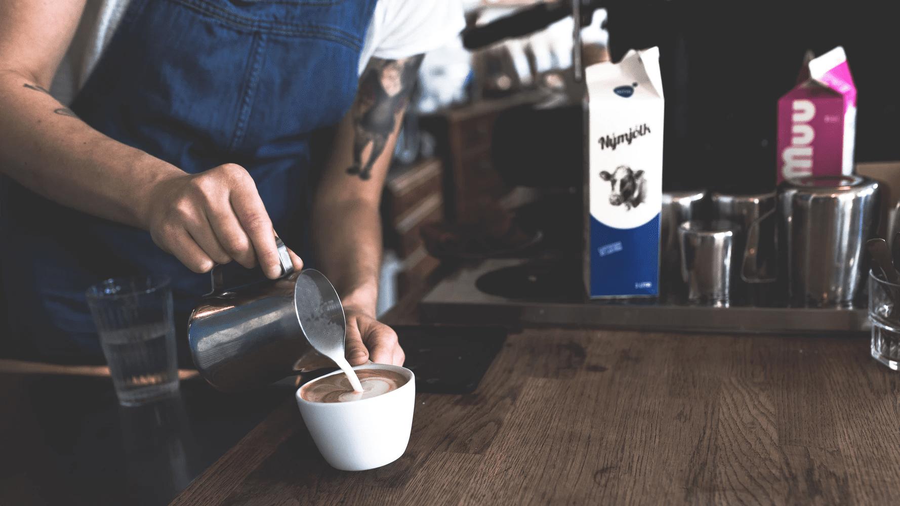 barista pouring milk on a espresso to make a cappuccino