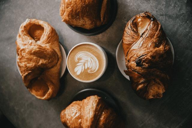 un latte y varios panes y productos de pasteleria