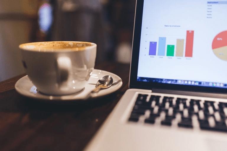 una taza de cafe y un computador