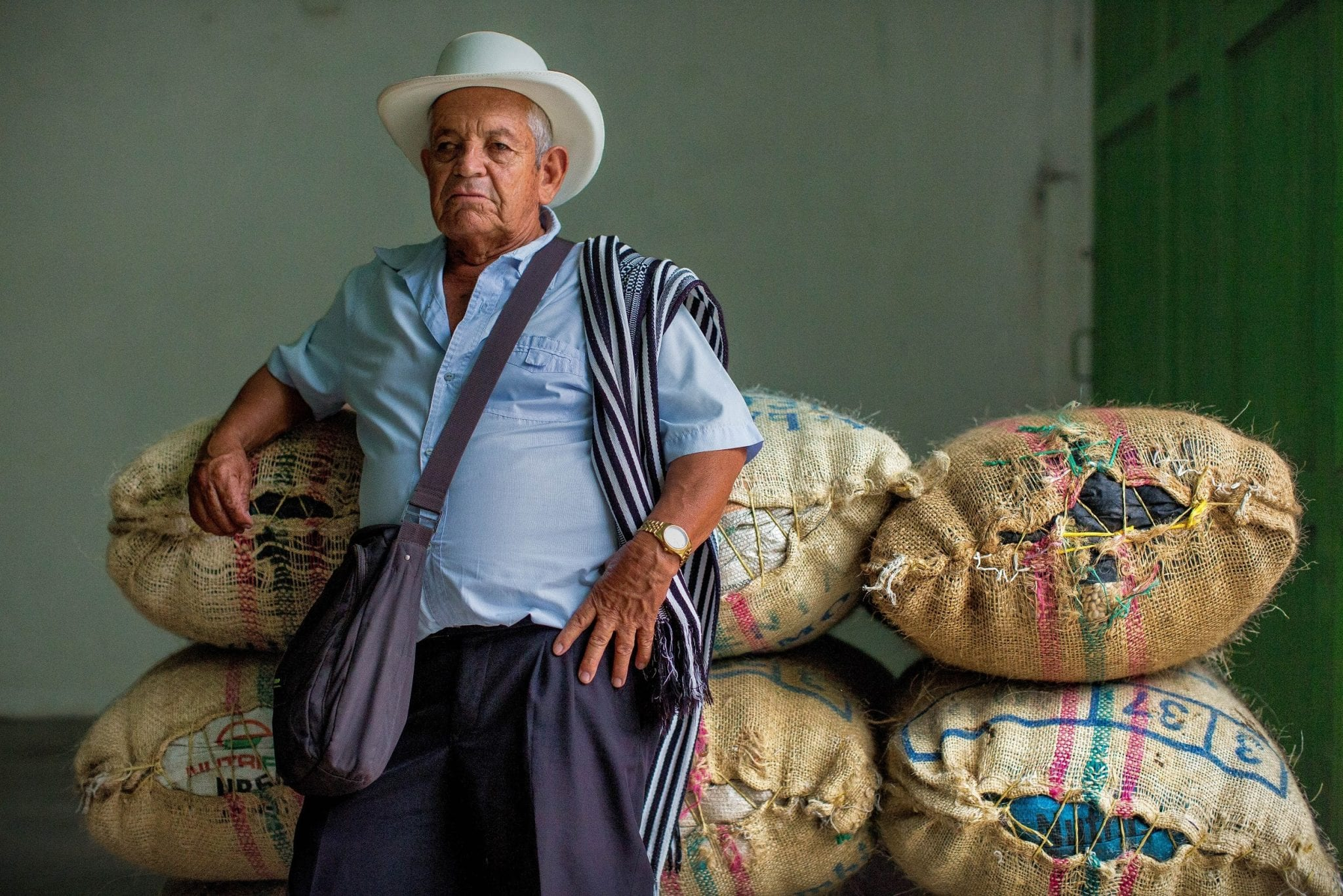 coffee farmer next to his coffee bags that are going to be exported
