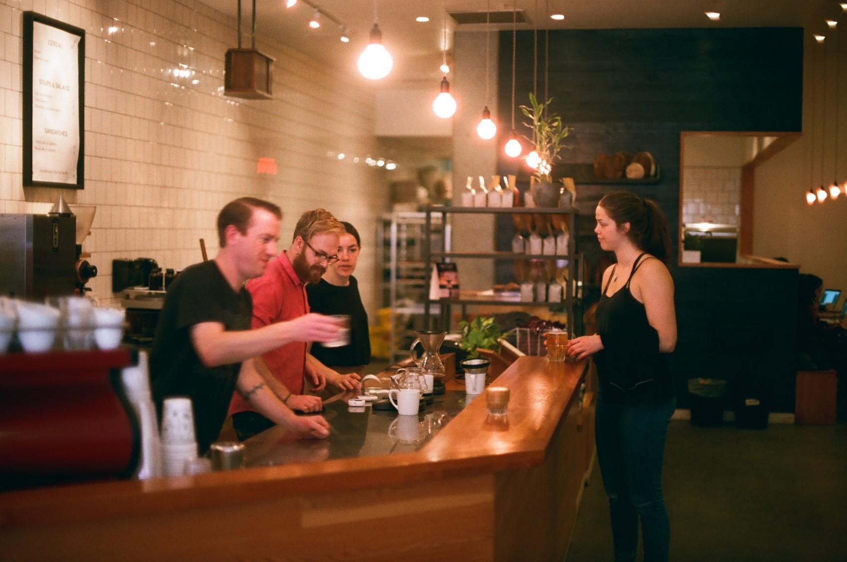 clientes de cafe recibiendo su cappuccino