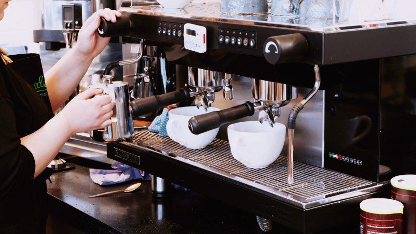 un barista crema leche para hacer un cafe latte
