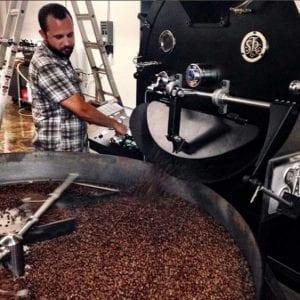 roaster releasing coffee into cooling bin