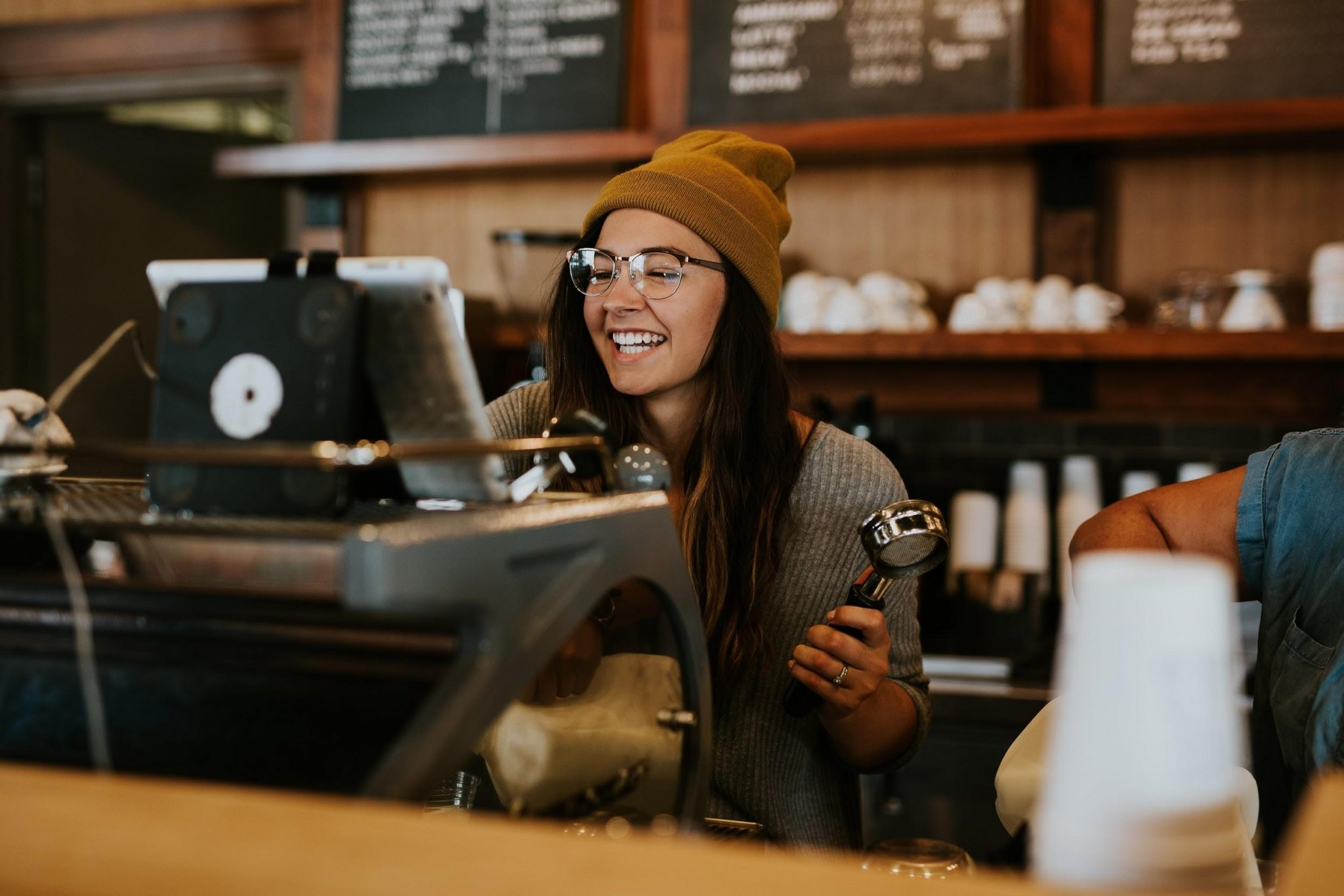 una barista destras de la barra de cafe
