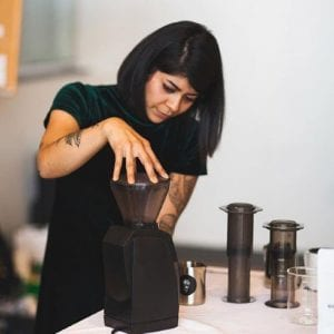 woman grinding coffee on baraza grinder to brew on aeropress