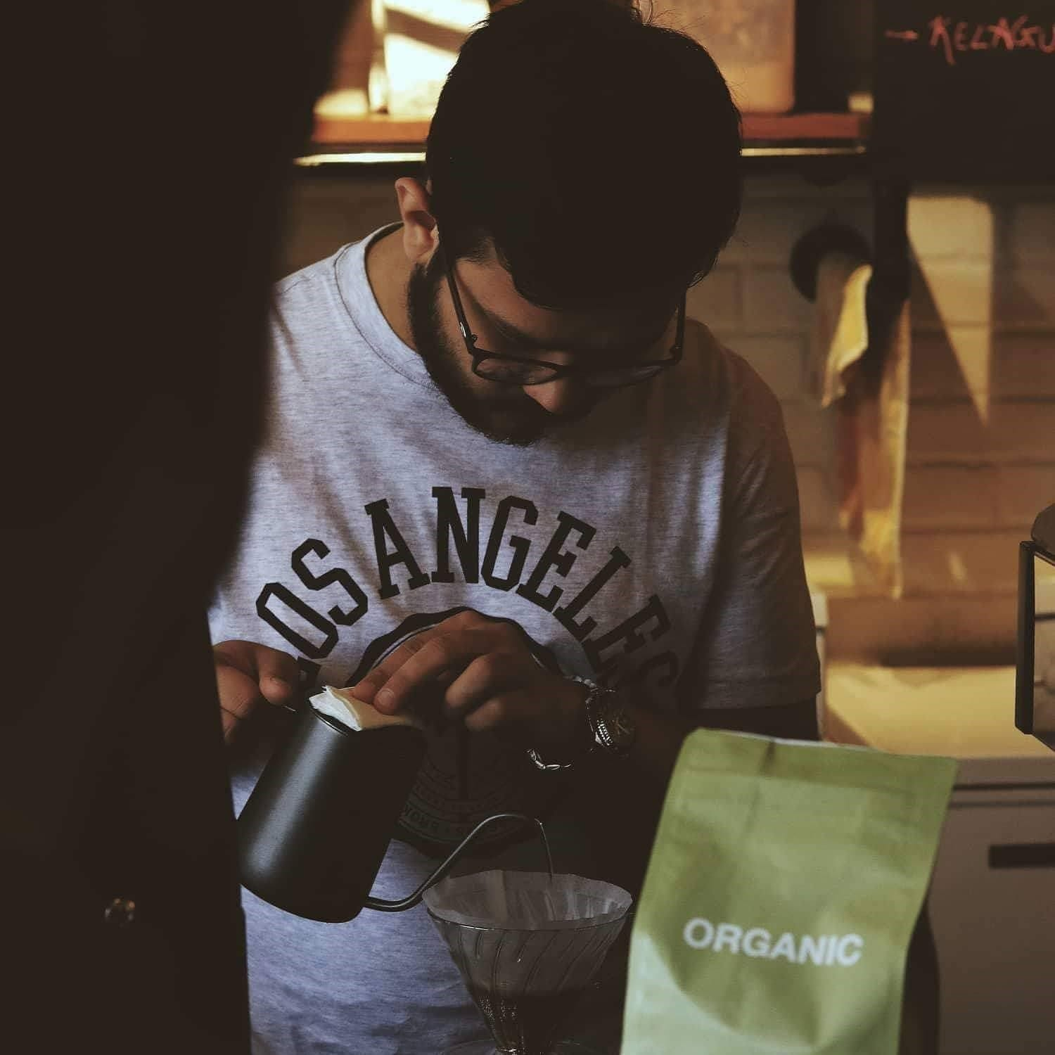a barista brews on a V60 for a client
