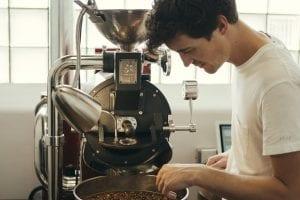 roaster inspecting fresh batch of roasted coffee