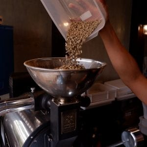 pouring green beans into coffee roaster